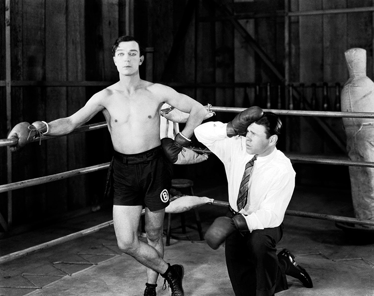 """Buster Keaton and World Middleweight Champion, Mickey Walker, on the set of """"Battling Butler"""" (1926)."""