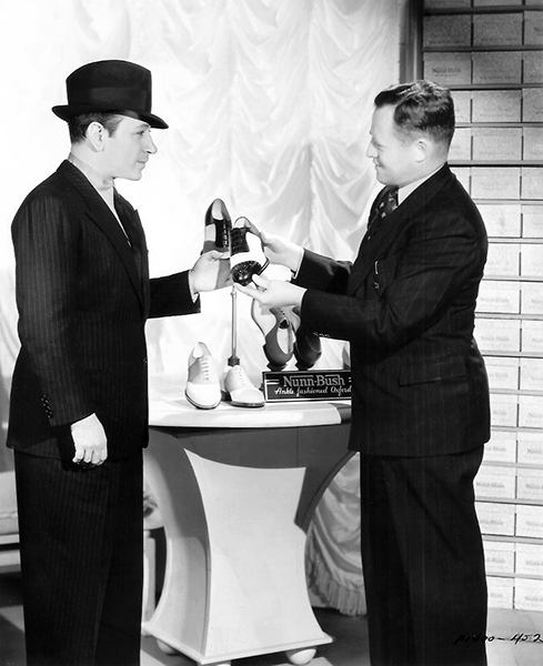 """George Raft was one of several celebrities promoting Nunn-Bush shoes in 1938. According to shoemaker Emidio Spezza, he had small feet and wore size 7.5 B. In this photo he is admiring the """"Gotham."""" Bizarre Los Angeles."""