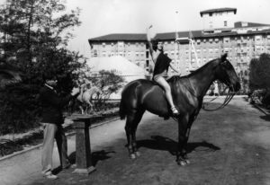 """Mrs. Mildred Perlee, a dancer whose stage name is """"Aarai,"""" poses on Dexter, a light cavalry horse owned by Major Sands of the 82nd Field Artillery, Ft. Bliss, Texas. The artist is L.P. Prescott, who is working on a sculpture of """"Joan of Arc."""" Photo was taken in 1928 on the Ambassador Hotel grounds. (Bizarre Los Angeles)"""