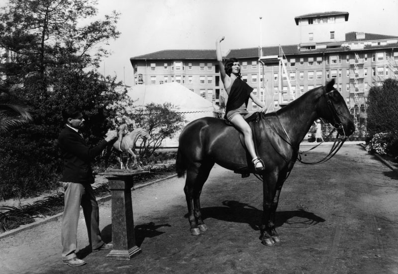 "Mrs. Mildred Perlee, a dancer whose stage name is ""Aarai,"" poses on Dexter, a light cavalry horse owned by Major Sands of the 82nd Field Artillery, Ft. Bliss, Texas. The artist is L.P. Prescott, who is working on a sculpture of ""Joan of Arc."" Photo was taken in 1928 on the Ambassador Hotel grounds. (Bizarre Los Angeles)"