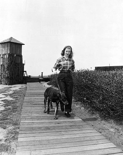 Veronica Lake walking a doberman in 1946. (Bizarre Los Angeles)
