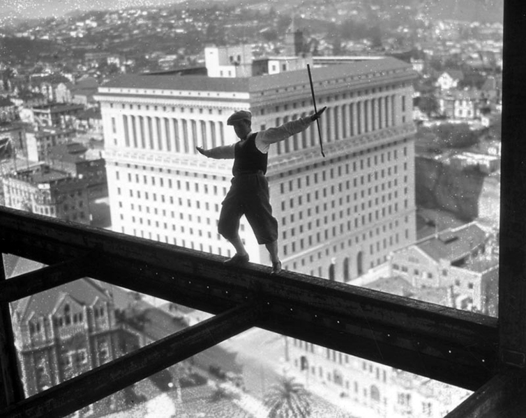 A stunt man, wearing golfing attire and holding a golf club, is photographed on a girder of the present L.A. City Hall while under construction in 1927. (LAPL) Bizarre Los Angeles