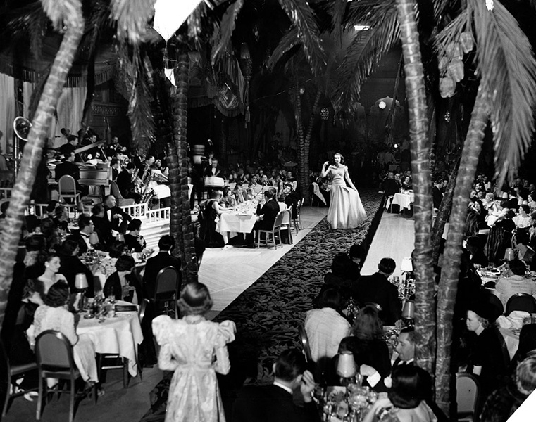 """Fashion Fortnight"" at the Cocoanut Grove held on January 27, 1938. Ruth Stevens is the model, sporting a spring negligee of white jersey embroidered with rhinestones. (Bizarre Los Angeles)"