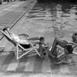 """Model Mothers"" with the Blue Book Model Agency lounge with two children at the Ambassador Hotel's Lido swimming pool in 1945. (Photo: Ralph Morris/LAPL)"