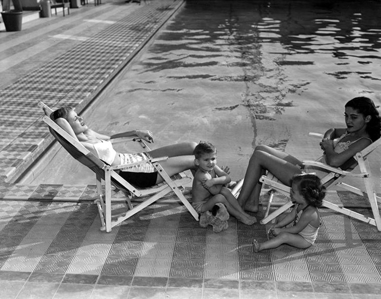 """""""Model Mothers"""" with the Blue Book Model Agency lounge with two children at the Ambassador Hotel's Lido swimming pool in 1945. (Photo: Ralph Morris/LAPL)"""
