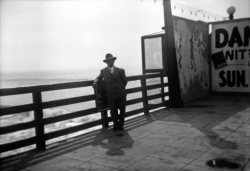 A man poses next to a couple of signs for the Aragon Ballroom, which was located on Lick Pier in Santa Monica. Photo, circa 1947.