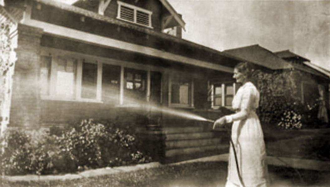 Woman watering her lawn in 1915