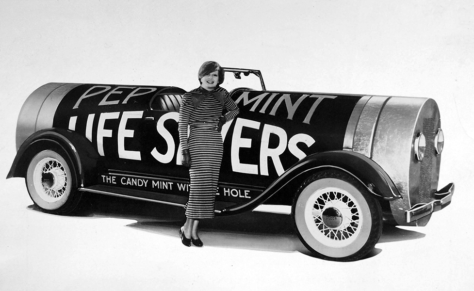 Film player Sari Maritza posing in front of the Life Savers car.  (Bizarre Los Angeles)