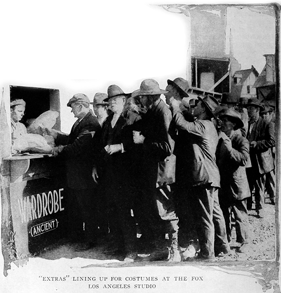 Movie extras lining up for costumes at the Fox Studio lot in Edendale (Los Feliz). Photo, circa 1916-1918. At that time, they were paid $5/day. If an Extra was promoted to a film character, his/her pay went up to $7.50 to $10 per working day. (Bizarre Los Angeles)