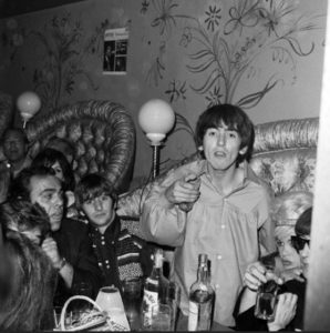 George Harrison throws a drink at a pesky photographer at the Whiskey-a-Go-Go on August 26, 1964. Sandwiched between Harrison and John Lennon sits Jayne Mansfield. Apparently, the drink missed the photographer but hit Mamie Van Doren sitting nearby…(Bizarre Los Angeles)