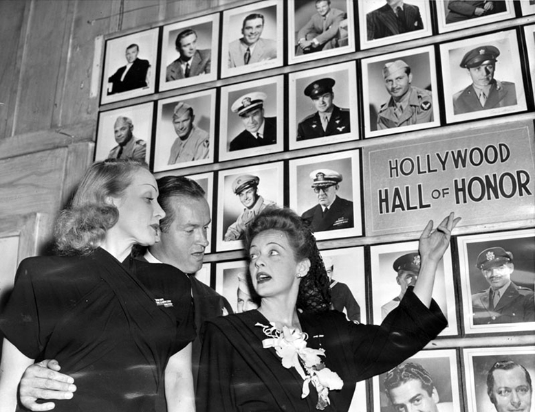 "Marlene Dietrich, Bob Hope and Bette Davis standing in front of the Hollywood Hall of Honor at the Hollywood Canteen. The original building used to be a livery stable that had been converted into a nightclub called ""The Old Barn"" before becoming the Canteen. This photo was taken on November 3,1943, and features a Who's Who of entertainment professionals who entered the armed forces in WWII. (LAPL) Bizarre Los Angeles"