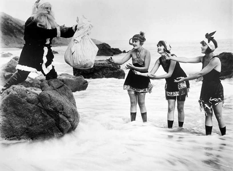 Phyllis Haver (left) and two other Mack Sennett Bathing Beauties greet a Creepy Santa on the beach. (Bizarre Los Angeles)
