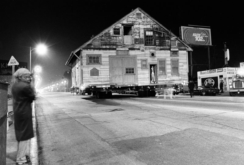 A late night move of the Lasky-DeMille Barn from Paramount Studios to a vacant lot on Vine Street in late October 1979.  Bogie's Liquor store's address is at 5373 Melrose Avenue. The barn was donated to the Hollywood Chamber of Commerce's Historic Trust, which envisioned it being a museum devoted to Jess Lasky, Cecil B. DeMille and Samuel Goldwyn. The building later moved from Vine Street to his current location on Highland Ave., across from the Hollywood Bowl. It's now called the Hollywood Heritage Museum. (LAPL) Bizarre Los Angeles
