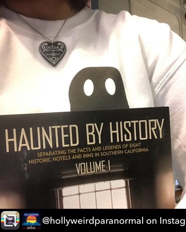 Tammie of the Hollyweird Paranormal podcast with a copy of Haunted by History Vol. 1.