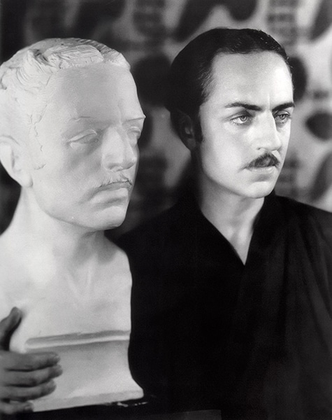 William Powell poses next to a bust of himself in 1928. (Bizarre Los Angeles)
