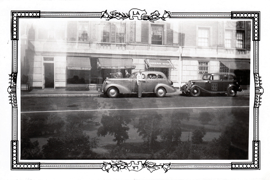 A 1937 Studebaker sedan is parked in front of a dress ship in Los Angeles. Bizarre Los Angeles
