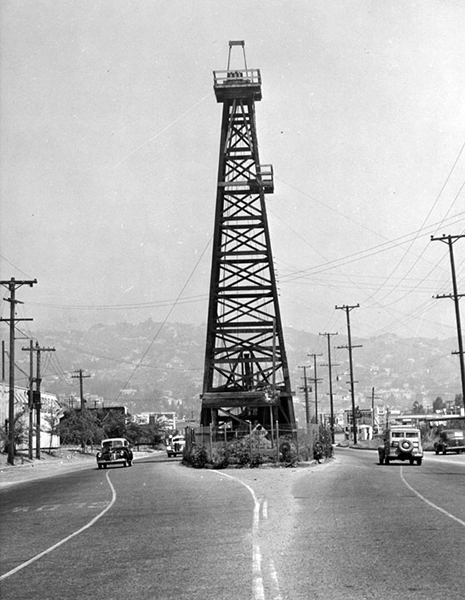 """Oil Island"" was located on La Cienega Blvd., between Beverly and 3rd Street. The wooden derrick was originally constructed in 1907 in the middle of a bean field. When the city extended La Cienega to Sunset Blvd., there was a dispute over the cost of the well, so the city built around it. In 1946, an agreement was struck and the well was dismantled. (Bizarre Los Angeles)"
