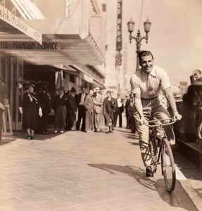 Buster Crabbe bicycling near the corner of Hollywood and Vine in 1933. To the left of Crabbe is the Equitable Building located at 6253 Hollywood Blvd. In the back ground, the Pantages Theater marquee is visible–barely. (Bizarre Los Angeles)