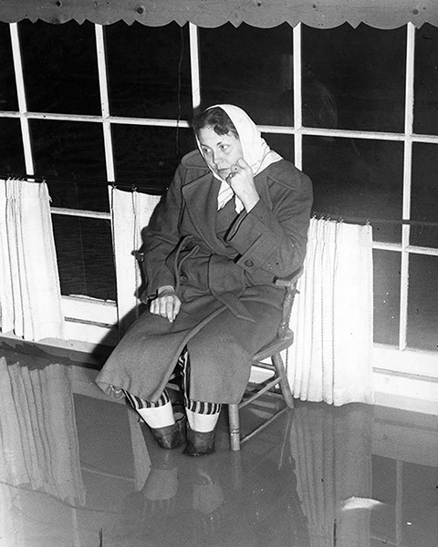 Mrs. Robert Sullivan sitting inside her flooded Sun Valley Home in 1962 after a heavy downpour. (Photographer: Alan Hyde / LAPL 00112352)
