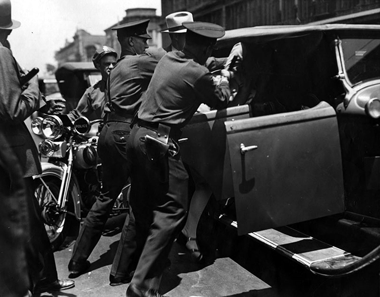 "Members of LAPD Captain Hynes' ""Red"" squad throwing a woman in the back of a car during an attempted political meeting at the Plaza on June 28, 1932. William Foster, the Communist political candidate for U.S. President at the time, had legally tried to get a permit to speak at the Plaza, but had been denied. Frustrated by the lack of cooperation, he announced that he would be there anyway at noon. The picture tells the rest of the story. (LAPL: 00039797) Bizarre Los Angeles"