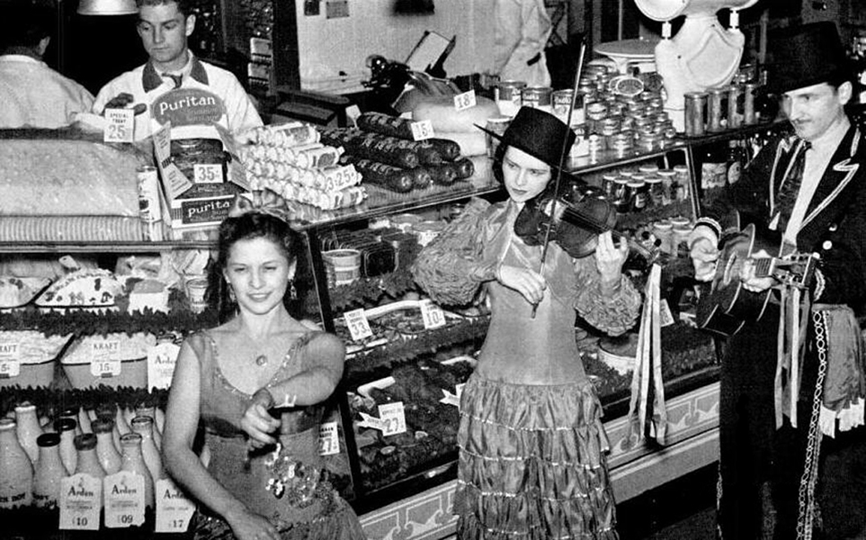 """Fandangos and salami were offered cheek by jowl at the opening of Rancho Pico, a super-market in Los Angeles. Super-markets, fearing that their customers have become too jaded to be attracted by conventional searchlight displays, now put on floor shows with their weekend sales. The Otto K. Olesen Illuminating Co., which supplies the searchlights, also produces the floor shows."" -- LIFE Magazine, November 1938. (Bizarre Los Angeles)"