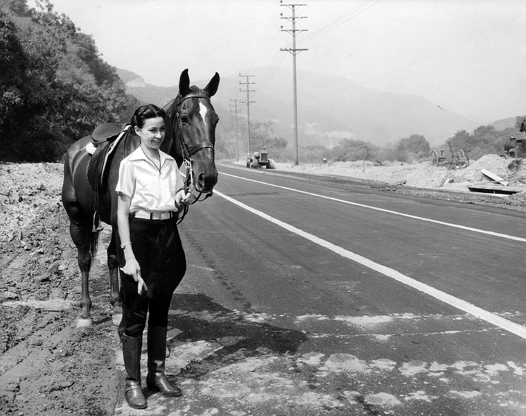 "Photo is dated Oct. 19, 1935, with a caption that reads: ""Celebrating the completion of a modern highway over one of Los Angeles' oldest trails, Sepulveda highway will be dedicated Sunday with gay fiesta where the highway joins with Sunset boulevard. Angeline Pagones is shown with her horse on the bridle path inspecting the new roadway. The highway follows a trail used ceturies [sic] ago by the Indians on their way to the sea."" Bizarre Los Angeles."