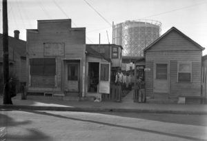 A slum in L.A., circa 1938. The address appears to be 311 N. Mission Road. The small room with the open door is a shoe repair shop. (UCLA) Bizarre Los Angeles