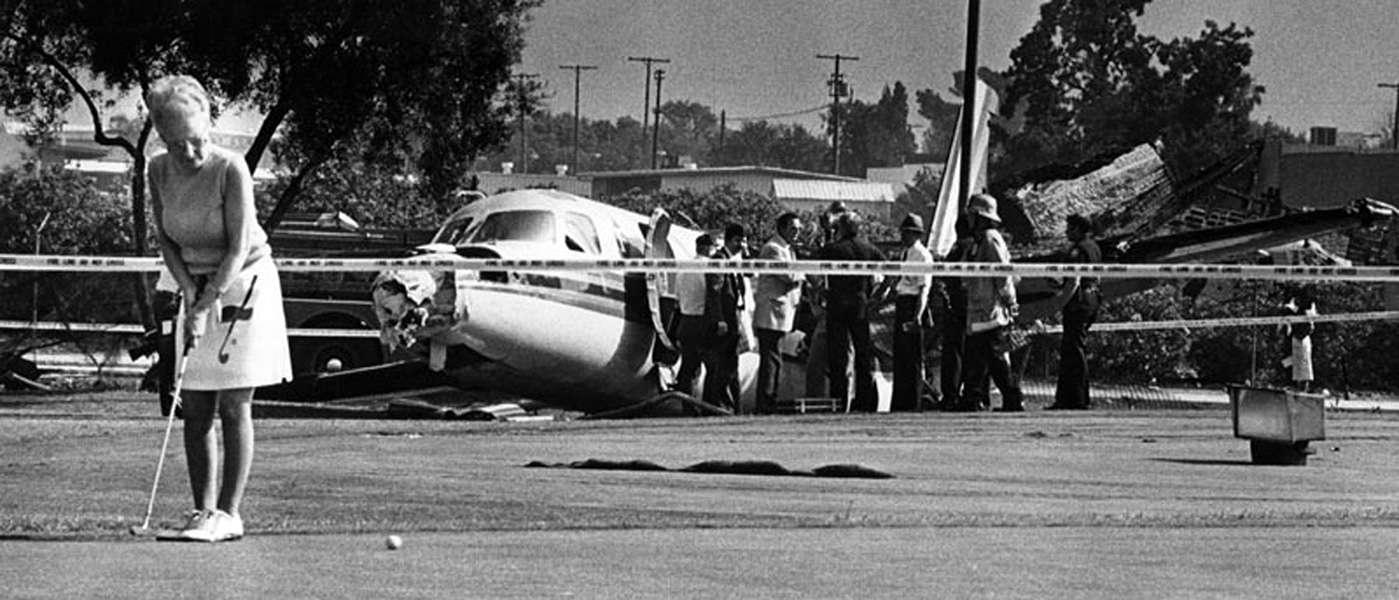 Not even a plane wreck interferes with Minnie Cook's golf game at the Van Nuys Golf Course. The plane was attempting to land at the Van Nuys airport when its hydraulic system malfunctioned, preventing the brakes from working. The out of control plane sped off the runway, hit a couple of automobiles and smashed through a fence, finally coming to a stop near the 14th hole. No one was injured, including the pilot, James Mayfield. The incident took place in June of 1985. (Photographer: Mike Mullen/ LAPL:00094894 (Bizarre Los Angeles)