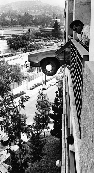 An embarrassing mishap in a parking garage near the County-USC Medical Center on July 31, 1985. The driver of a Ford Fairmont station wagon accidentally pressed the gas pedal instead of the brake, crashing through a cement barrier and metal railing. The vehicle teetered about 200 feet above the ground while the driver was able to get out of the car. What kept the station wagon from falling was a steel cable that ran along the edge of the parking garage. (Photographer: Chris Gulker / LAPL: 00094973) Bizarre Los Angeles