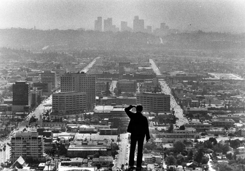 Frank Oklesson, visiting from Georgia, stands on top of a hill near Wander View and Aspen Oak Lane. Below him is a 1985 view of Glendale as well as the downtown Los Angeles skyline in the distance. (Photographer: Mike Sergieff / LAPL 00043662 ) Bizarre Los Angeles.