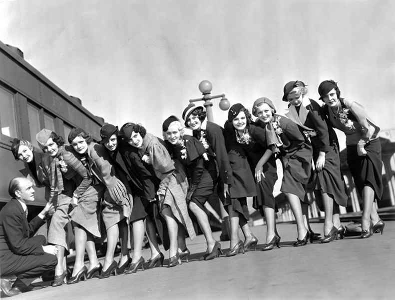 At the Southern Pacific Station, theatrical producer Earl Carroll poses with chorus girls hired to appear in the Paramount film Murder At The Vanities (1934). The girls are (left to right): Evelyn Kelly, Dorothy Dawes, Ernestine Anderson, Ruth Hilliard, Beryl Wallace, Marion Callahan, Laurie Shevlin, Wanda Perry, Constance Jordan, Anya Taranda and Leda Nacova. (LAPL) Bizarre Los Angeles